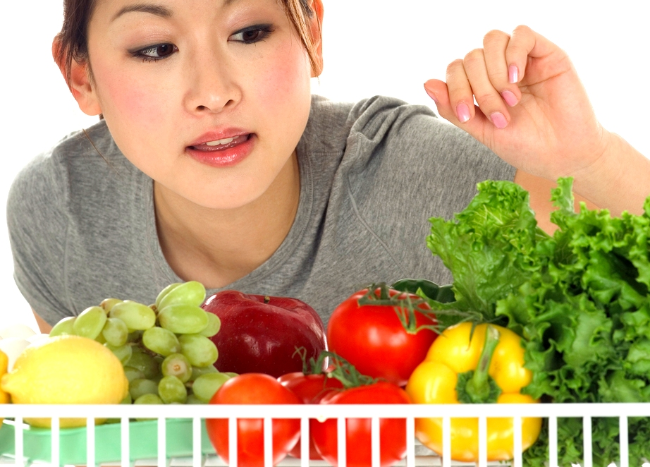 Woman Looking at Vegetables in Refrigerator ca. 2003